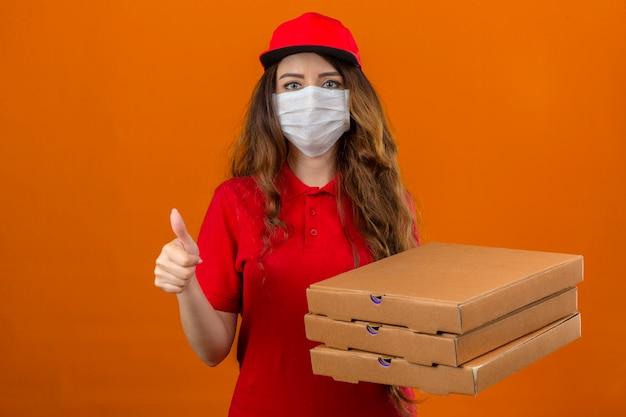 Jonge leveringsvrouw die rood poloshirt en glb in medisch beschermend masker dragen die zich met stapel pizzadozen bevinden die duim over geïsoleerde oranje achtergrond tonen
