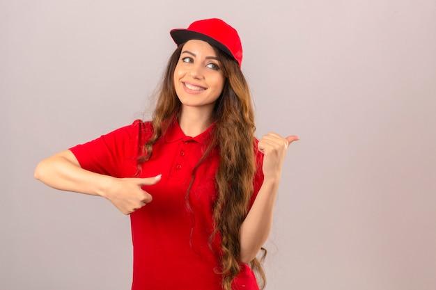 Jonge leveringsvrouw die rood poloshirt en pet draagt die met gelukkig gezicht glimlacht en naar de kant kijkt met duim omhoog over geïsoleerde witte achtergrond