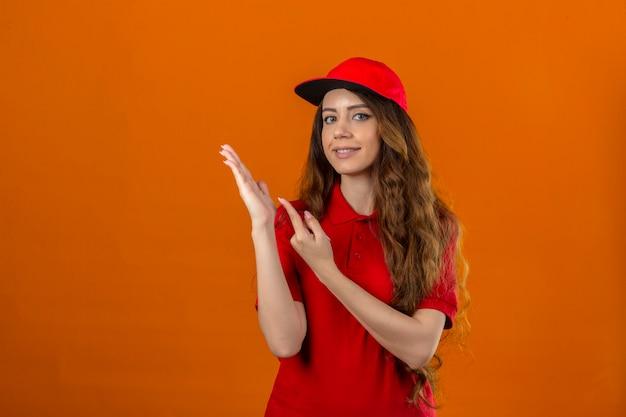 Jonge leveringsvrouw die rood poloshirt en pet draagt die naar de camera glimlacht terwijl zij met hand presenteert en met vinger over geïsoleerde oranje achtergrond richt