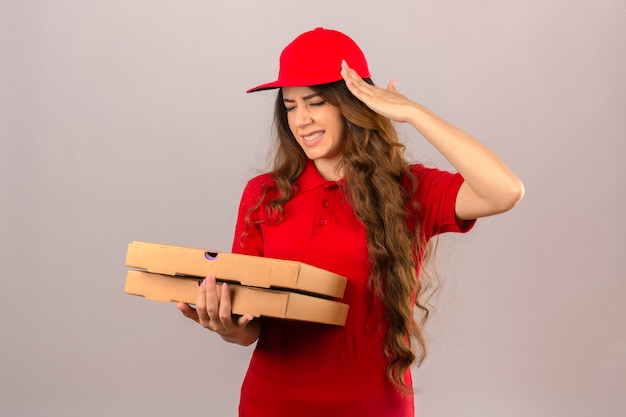 Jonge leveringsvrouw die rood poloshirt en pet draagt die onwel aanraken van hoofd die aan hoofdpijn lijden over geïsoleerde witte achtergrond