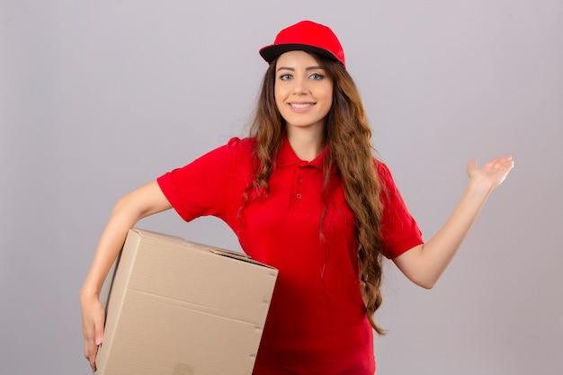 Jonge leveringsvrouw die rood poloshirt en pet draagt die zich met kartondoos bevindt die vrolijk glimlacht presenteert en met de palm van de hand richt die de camera over geïsoleerde witte achtergrond bekijkt