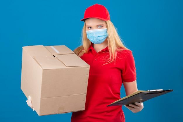 Jonge leveringsvrouw die rood poloshirt en pet in medisch beschermend masker draagt dat grote kartondoos en klembord houdt die camera met ernstig gezicht over geïsoleerde blauwe achtergrond bekijken