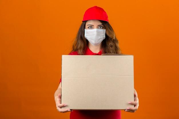 Jonge leveringsvrouw die rood poloshirt en pet in medisch beschermend masker draagt ?? dat zich met kartondoos bevindt die over geïsoleerde oranje achtergrond zelfverzekerd kijkt