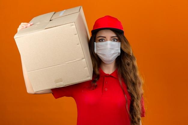 Jonge leveringsvrouw die rood poloshirt en pet in medisch beschermend masker draagt dat zich met kartondoos op schouder bevindt die over geïsoleerde oranje achtergrond kijkt