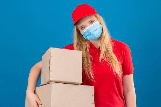 Jonge leveringsvrouw die rood poloshirt en pet in medisch beschermend masker draagt ?? dat zich met kartondozen bevindt die er moe en overwerkt over geïsoleerde blauwe achtergrond kijken