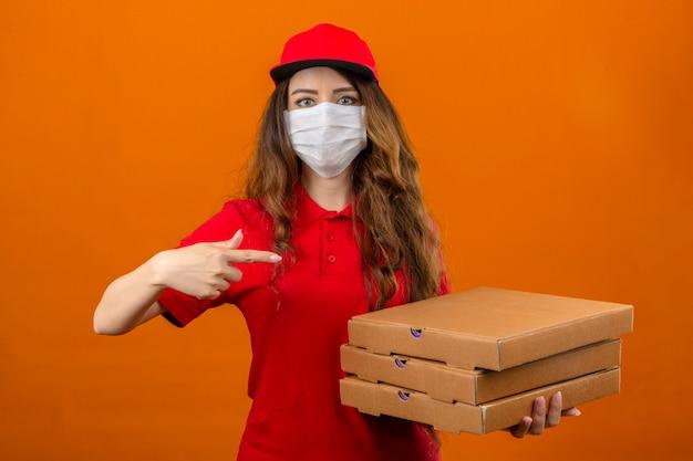 Jonge leveringsvrouw die rood poloshirt en pet in medisch beschermend masker draagt ?? die zich met stapel dozen bevindt en wijsvinger richt naar hen die camera met ernstig gezicht bekijkt over geïsoleerde oran