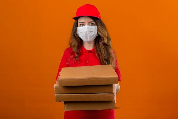 Jonge leveringsvrouw die rood poloshirt en pet in medisch beschermend masker dragen die zich met stapel pizzadozen bevinden die over geïsoleerde oranje achtergrond vertrouwen kijken
