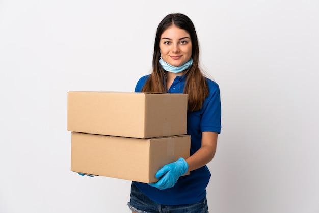 Jonge leveringsvrouw die tegen het coronavirus beschermt met een masker dat op wit wordt geïsoleerd dat veel glimlacht