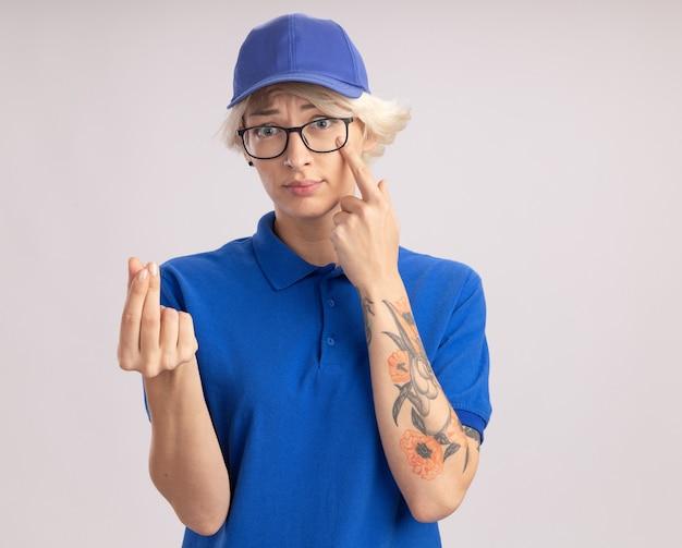 Jonge leveringsvrouw in blauw uniform en glb die glazen dragen die met vinger wijzen naar haar oog wrijven vingers die geldgebaar maken die zich over witte muur bevinden