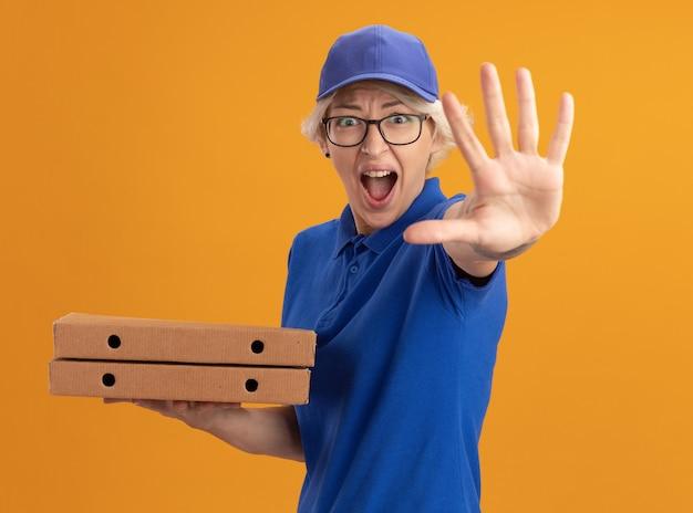 Jonge leveringsvrouw in blauw uniform en glb die glazen dragen die pizzadozen houden die stopgebaar maken met overhandigen oranje muur