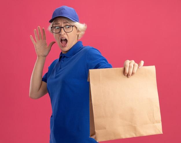 Jonge leveringsvrouw in blauw uniform en pet die glazen dragen die document pakket vasthouden en ernaar kijken in paniek de hand opheffen over roze muur
