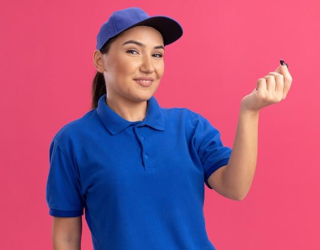 Jonge leveringsvrouw in blauw uniform en pet die naar voren kijken en geldgebaar wrijven vingers glimlachend zelfverzekerd staande over roze muur kijken