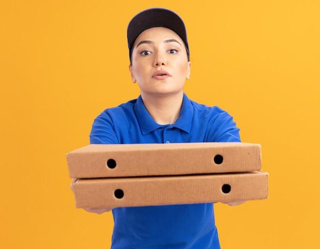 Jonge leveringsvrouw in blauw uniform en pet die pizzadozen houden die voorzijde met zelfverzekerde uitdrukking bekijken die zich over oranje muur bevindt