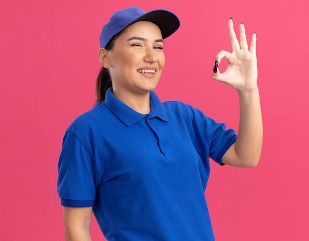 Jonge leveringsvrouw in blauw uniform en pet die voorzijde glimlachend vrolijk bekijkt tonend ok teken dat zich over roze muur bevindt