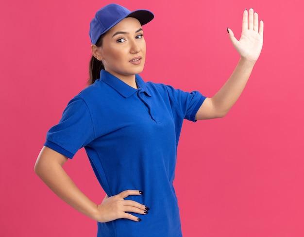 Jonge leveringsvrouw in blauw uniform en pet die voorzijde glimlachend zelfverzekerd opheffend open hand bekijkt die zich over roze muur bevindt