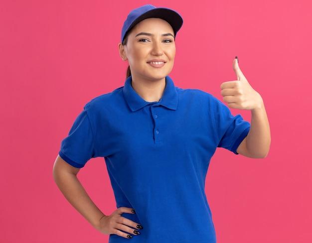 Jonge leveringsvrouw in blauw uniform en pet die voorzijde glimlachend zelfverzekerd zien zien thumbs up staande over roze muur kijken