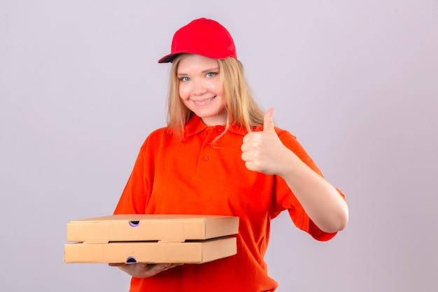 Jonge leveringsvrouw in oranje poloshirt en rode pet met pizzadozen die duim tonen die vrolijk over geïsoleerde witte achtergrond glimlachen