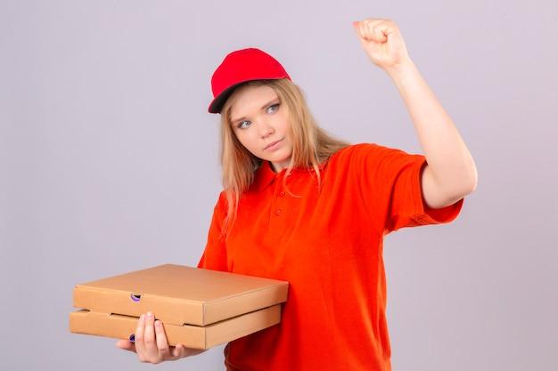Jonge leveringsvrouw in oranje poloshirt en rode pet met pizzadozen die vuist opheffen na een concept van de overwinningswinnaar over geïsoleerde witte achtergrond