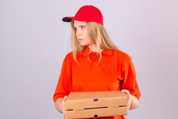 Jonge leveringsvrouw in oranje poloshirt en rood glb die pizzadozen houden die opzij fronsen over geïsoleerde witte achtergrond kijken