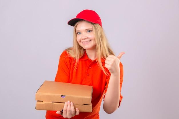 Jonge leveringsvrouw in oranje poloshirt en rood glb die zich met pizzadozen bevinden die duim tonen die vrolijk over geïsoleerde witte achtergrond glimlachen
