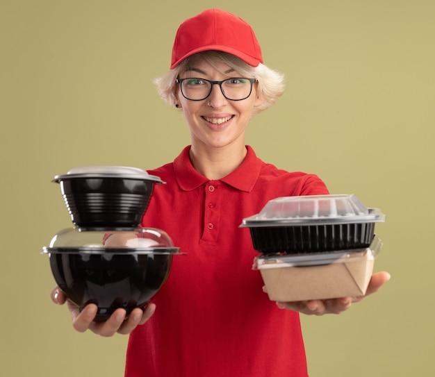 Jonge leveringsvrouw in rood uniform en glb die glazen dragen die voedselpakketten met glimlach op gezicht houden die zich over groene muur bevinden
