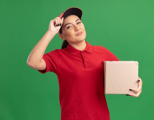 Jonge leveringsvrouw in rood uniform en glb die kartondoos houden die voorzijde met zekere glimlach bekijken die zich over groene muur bevinden
