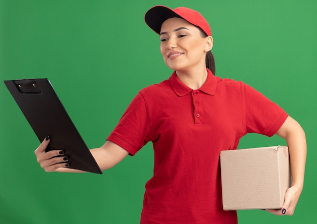 Jonge leveringsvrouw in rood uniform en glb die kartondoos met klembord houden die het met glimlach op gezicht bekijken die zich over groene muur bevinden