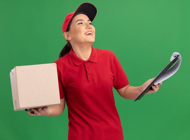 Jonge leveringsvrouw in rood uniform en glb die kartondoos met klembord houden die met glimlach op gezicht opzoeken die zich over groene muur bevindt