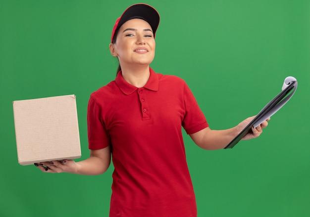 Jonge leveringsvrouw in rood uniform en glb die kartondoos met klembord houden die voorzijde glimlachend vrolijk status over groene muur bekijken