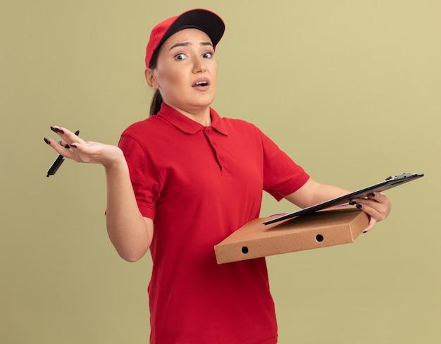 Jonge leveringsvrouw in rood uniform en glb die pizzadoos met klembord en potlood bekijken die zich voor verward status over groene muur bekijken
