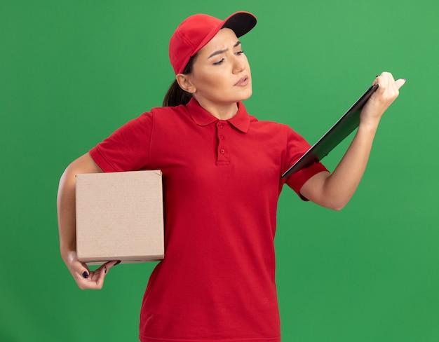 Jonge leveringsvrouw in rood uniform en glb met de kartondoos die van de klembordholding klembord met ernstig gezicht bekijkt dat zich over groene muur bevindt