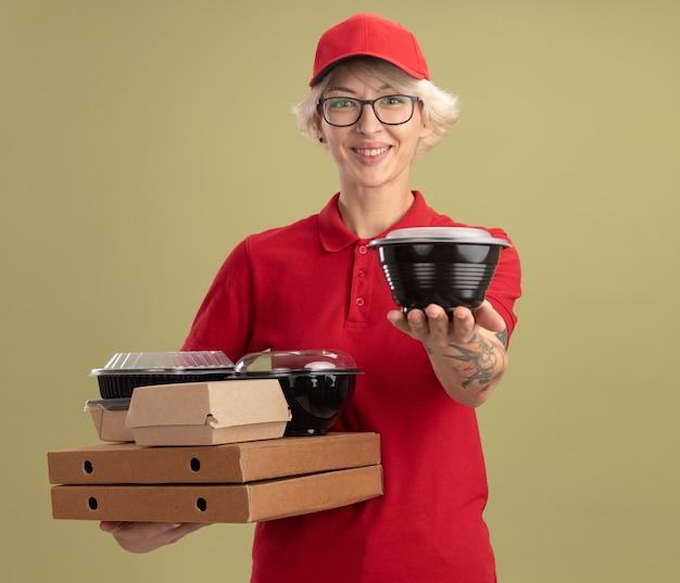 Jonge leveringsvrouw in rood uniform en pet die glazen draagt die pizzadozen en voedselpakketten houden die vrolijk glimlachen aanbiedend doos die zich over groene muur bevindt