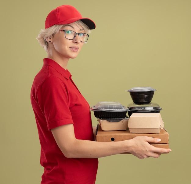 Jonge leveringsvrouw in rood uniform en pet die glazen draagt die pizzadozen en voedselpakketten houden die zijwaarts staan kijkend over groene muur zelfverzekerd
