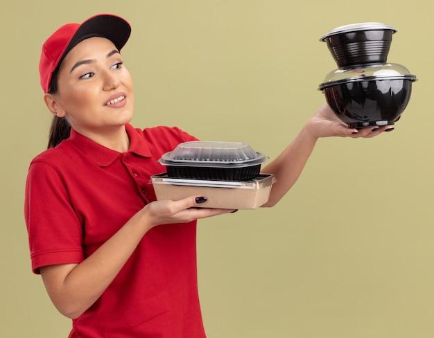 Jonge leveringsvrouw in rood uniform en pet die voedselpakketten houden die hen glimlachend met blij gezicht bekijken die zich over groene muur bevinden