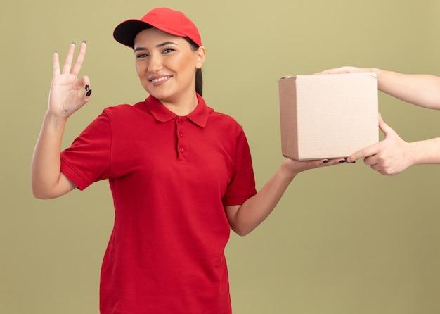 Jonge leveringsvrouw in rood uniform en pet die vriendelijk glimlachen tonend ok teken terwijl het ontvangen van doospakket zich over groene muur bevindt