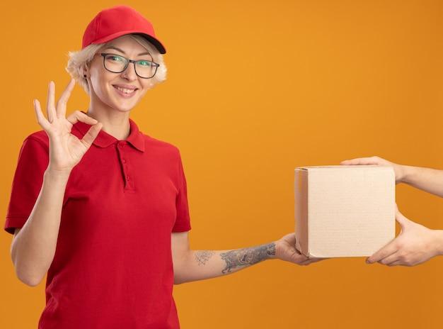 Jonge leveringsvrouw in rood uniform en pet die vriendelijk glimlachen tonend ok teken terwijl het ontvangen van doospakket zich over oranje muur bevindt