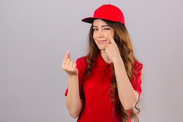 Jonge leveringsvrouw met krullend haar die rood poloshirt en glb dragen die een geldgebaar glimlachend vriendschappelijk over geïsoleerde witte achtergrond doen Gratis Foto
