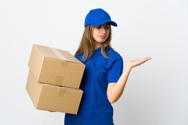 Jonge leveringsvrouw op geïsoleerde witte holding copyspace met twijfels