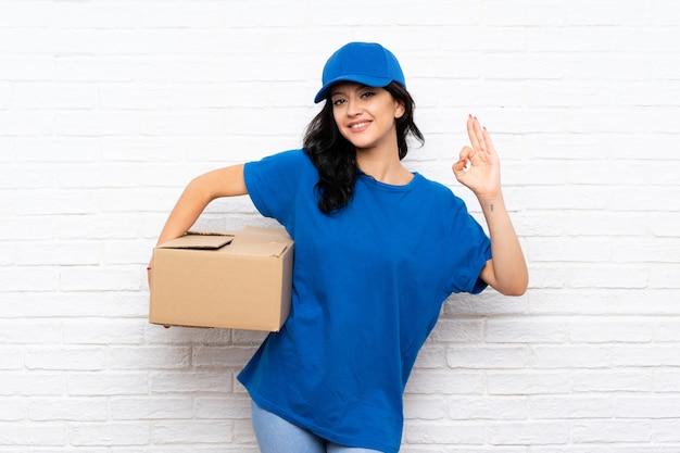 Jonge leveringsvrouw over bakstenen muur die ok teken met vingers tonen