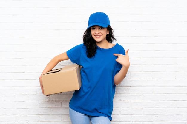Jonge leveringsvrouw over bakstenen muur met verrassingsgelaatsuitdrukking