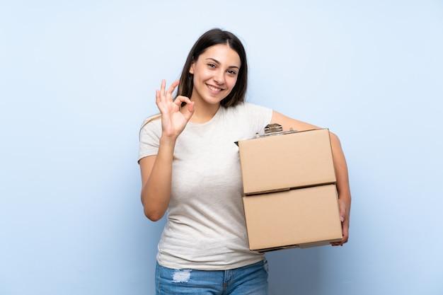 Jonge leveringsvrouw over blauwe bakstenen muur die ok teken met vingers tonen
