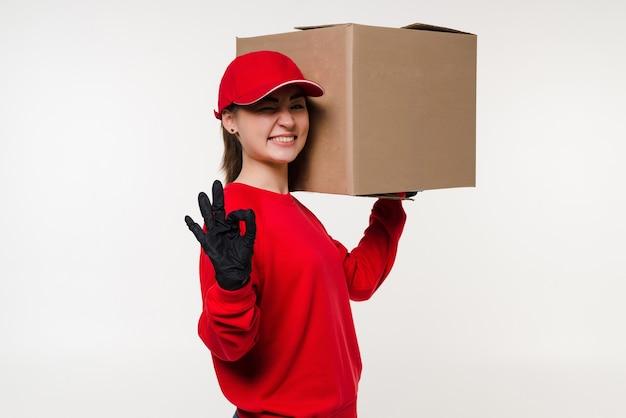 Jonge leveringsvrouw over geïsoleerde witte muur die een ok gebaar geeft
