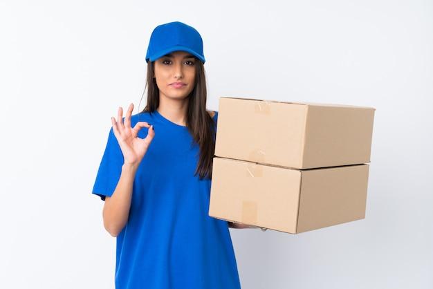 Jonge leveringsvrouw over geïsoleerde witte muur die een ok teken met vingers tonen