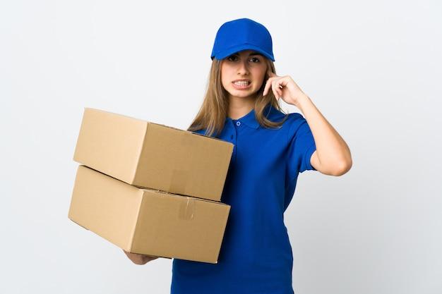 Jonge leveringsvrouw over geïsoleerde witte muur die en oren behandelt frustreert