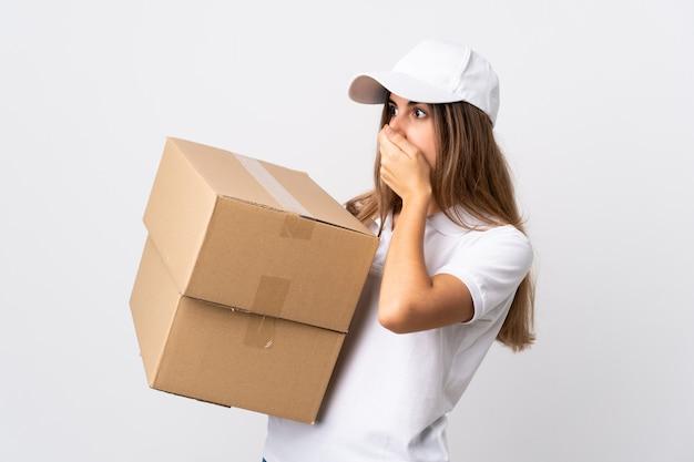 Jonge leveringsvrouw over geïsoleerde witte muur die mond behandelt en aan de kant kijkt