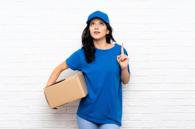 Jonge leveringsvrouw over witte bakstenen muur die de oplossing van plan zijn te realiseren terwijl het opheffen van een vinger