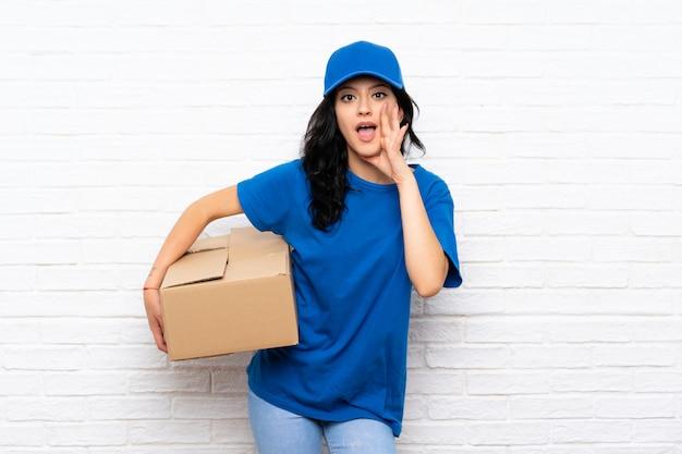 Jonge leveringsvrouw over witte bakstenen muur met verrassing en geschokte gelaatsuitdrukking