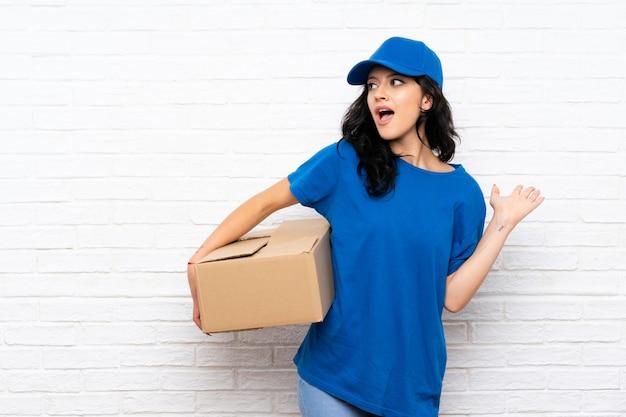 Jonge leveringsvrouw over witte bakstenen muur met verrassingsgelaatsuitdrukking
