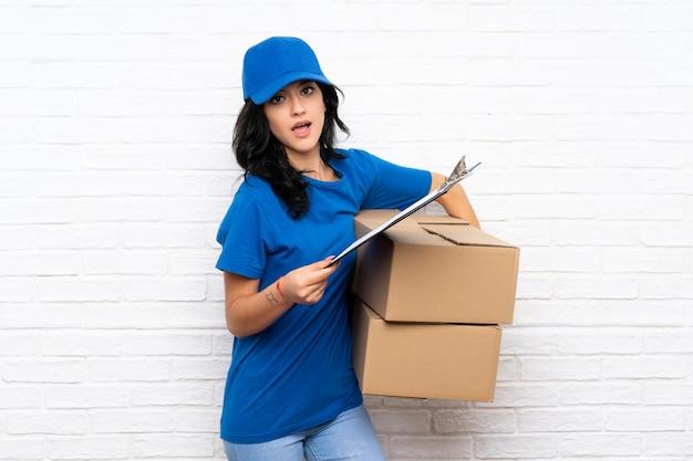 Jonge leveringsvrouw over witte bakstenen muur