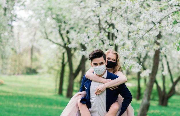 Jonge liefdevolle bruiden in park met medische maskers tijdens quarantaine op hun trouwdag